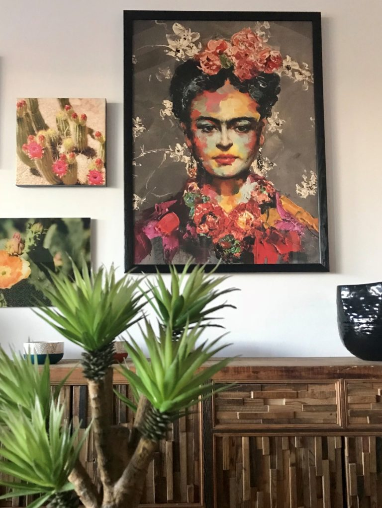 living space with eclectic painting of frida kahlo and desert plants