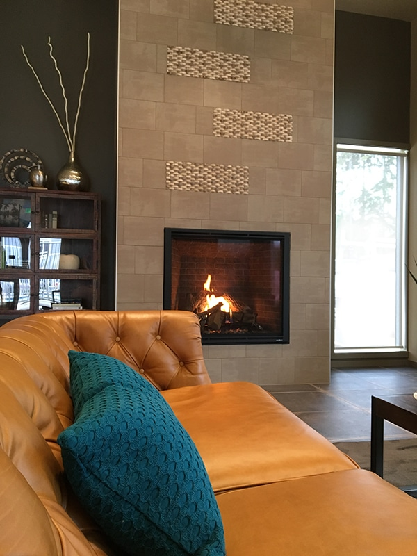 eclectic tiled fireplace and orange leather sofa