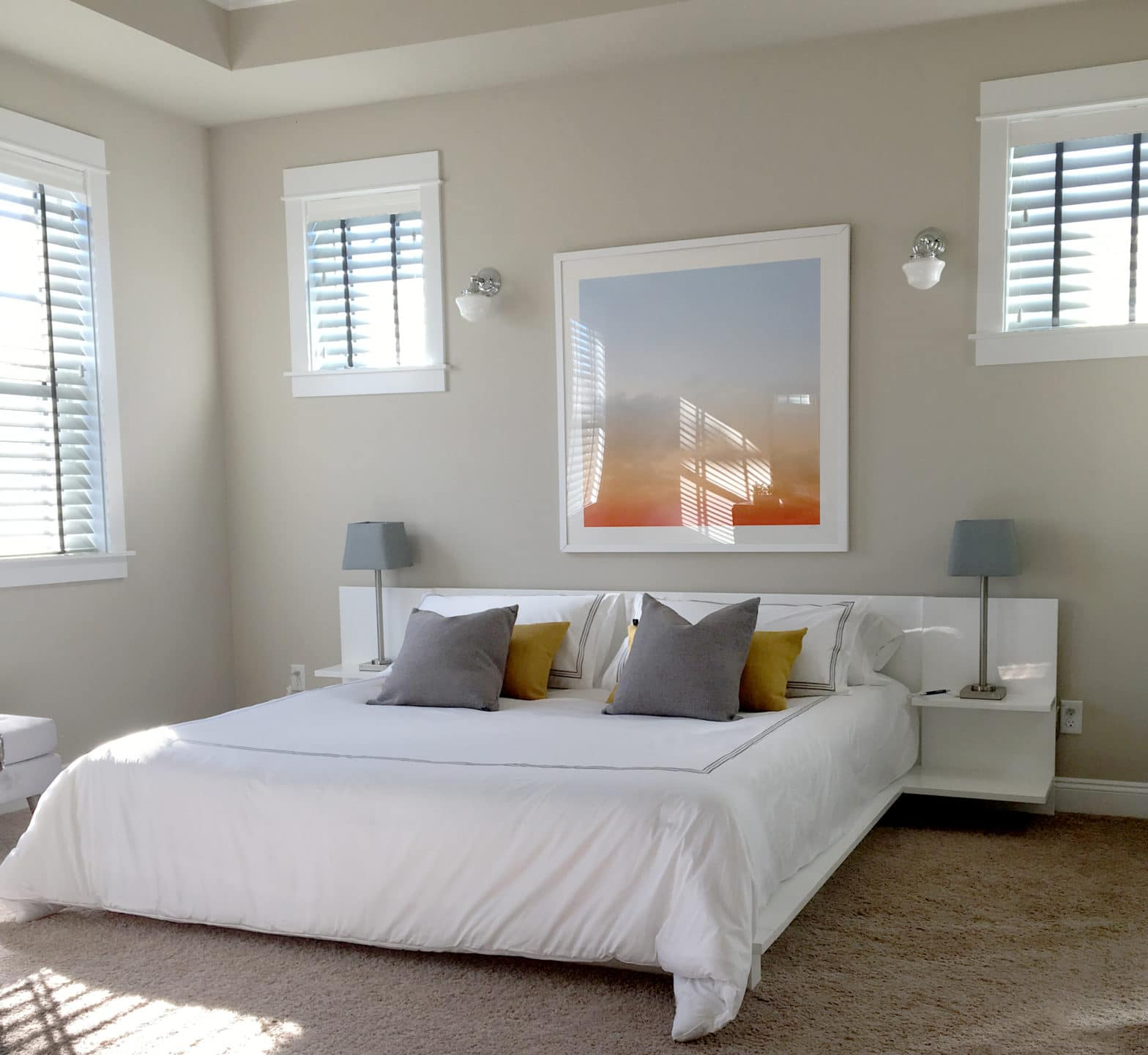 Light-filled master bedroom with colorful artwork