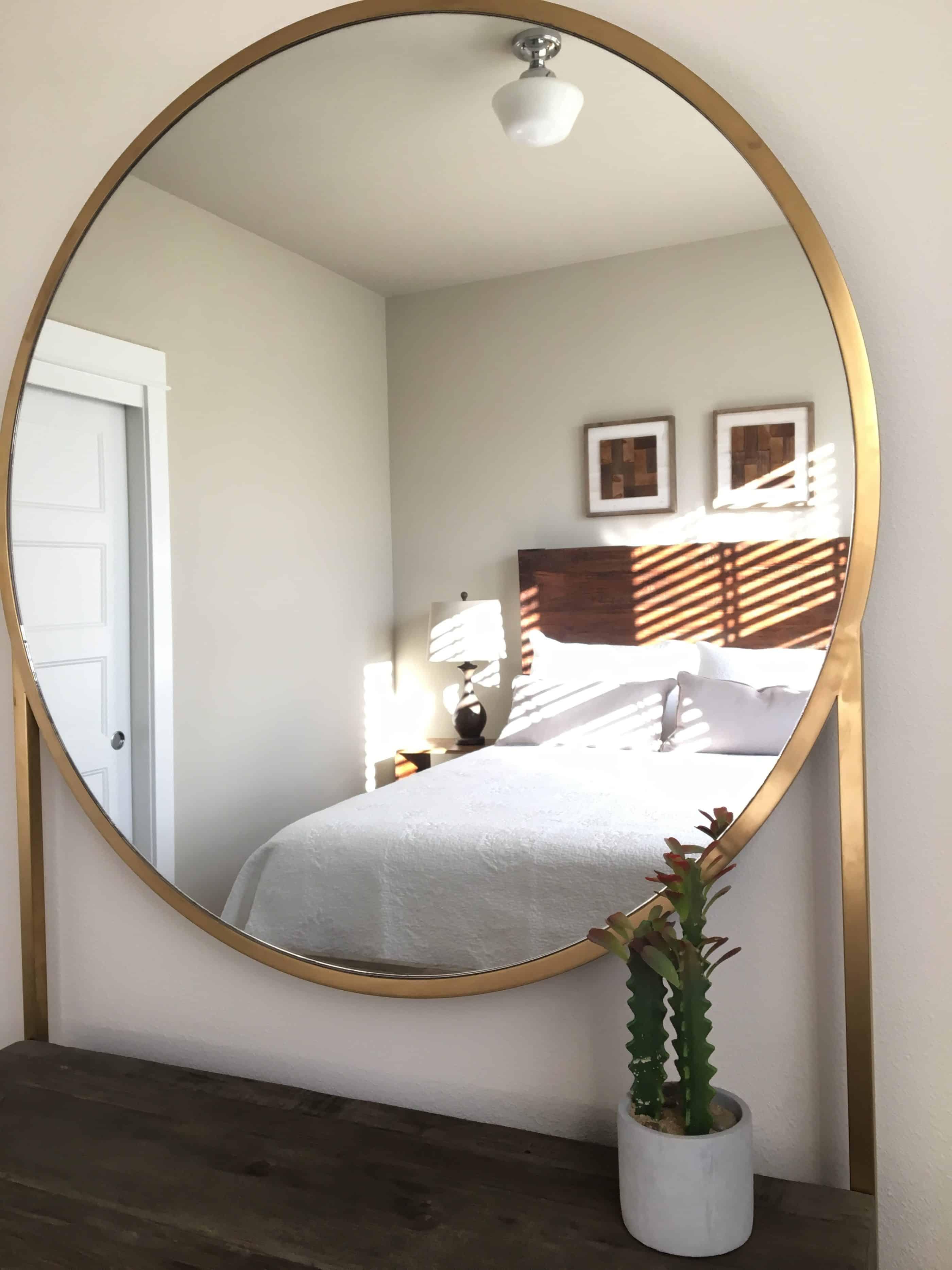 vacation rental design with round mirror on dresser