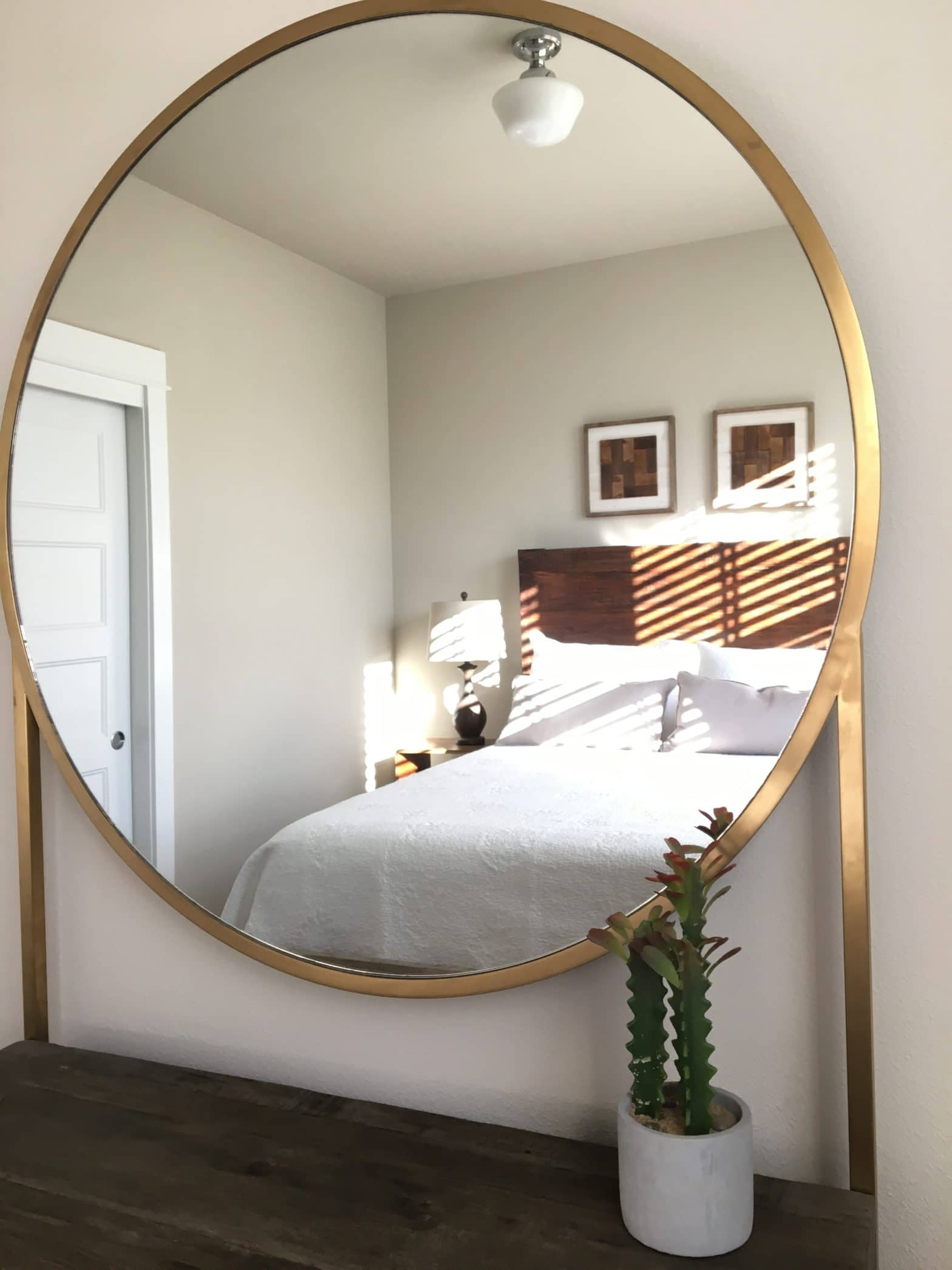 Round Mirror showing reflection of bed in vacation rental home