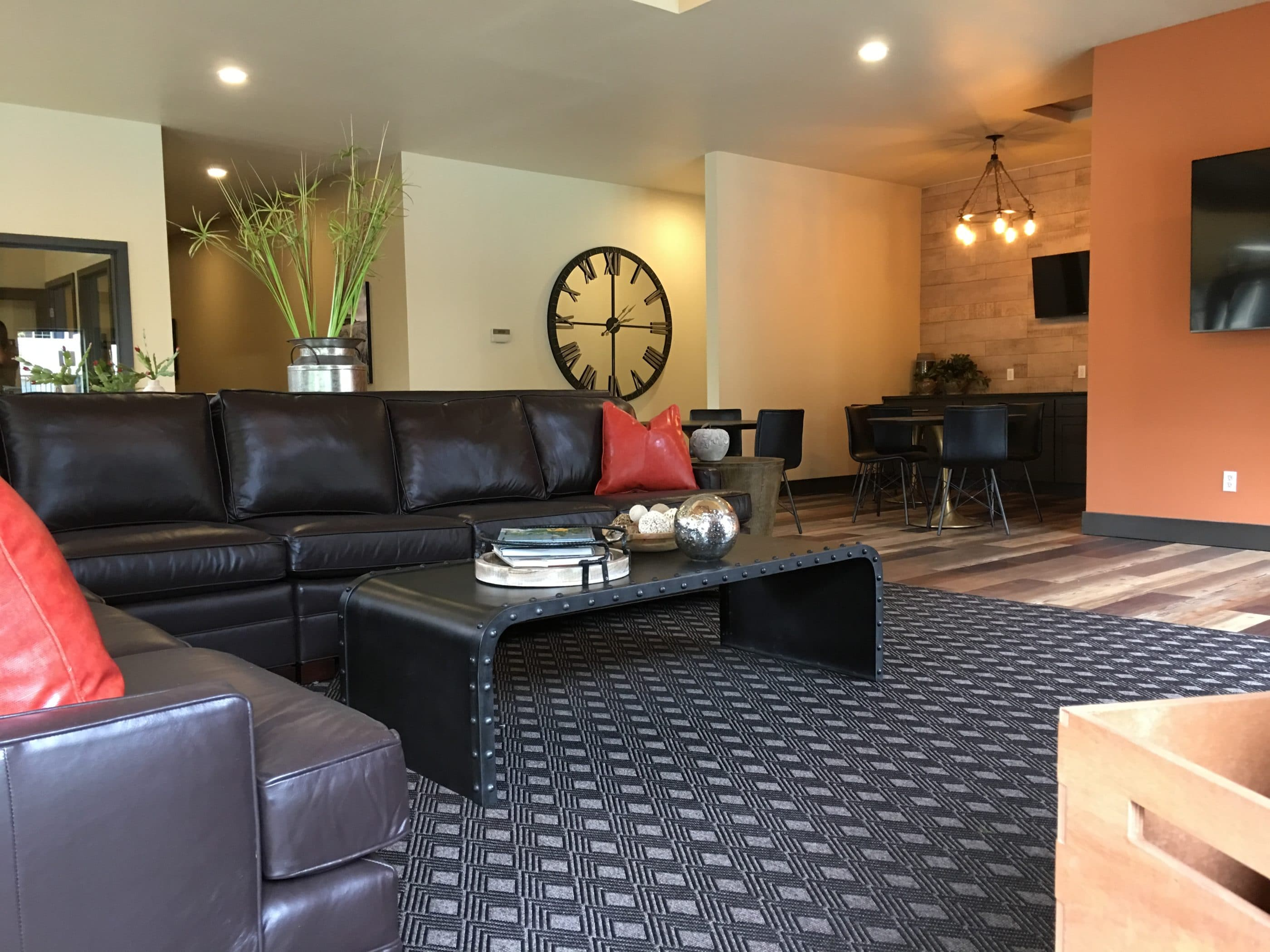 commercial interior design with black sectional and gray area rug