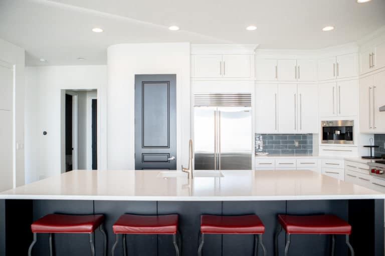 Modern Kitchen With White Cabinets and Red Counter Stools