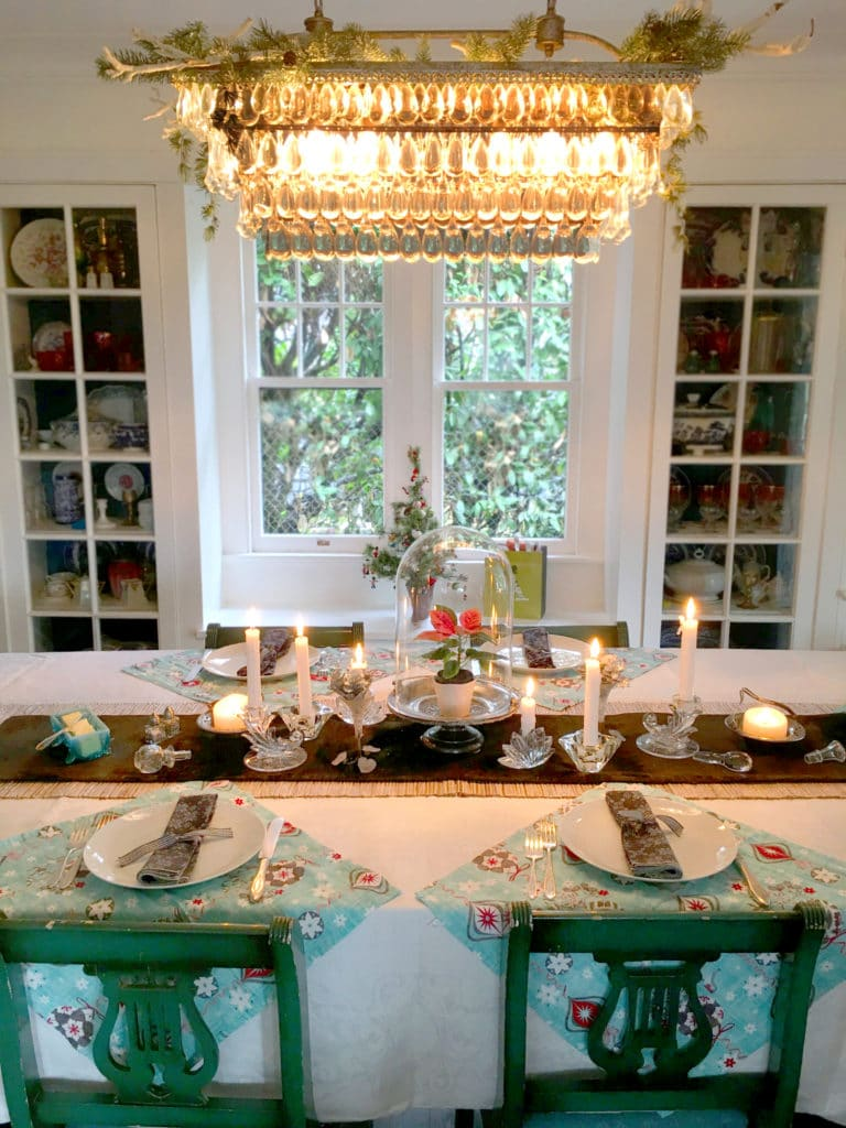 holiday table design with green chairs and chandelier