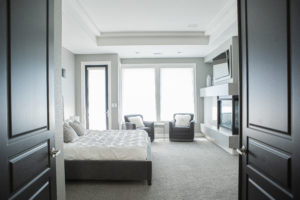 master bedroom interior with white bed and gray chairs