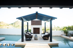 black patio furniture floating in pool under pergola