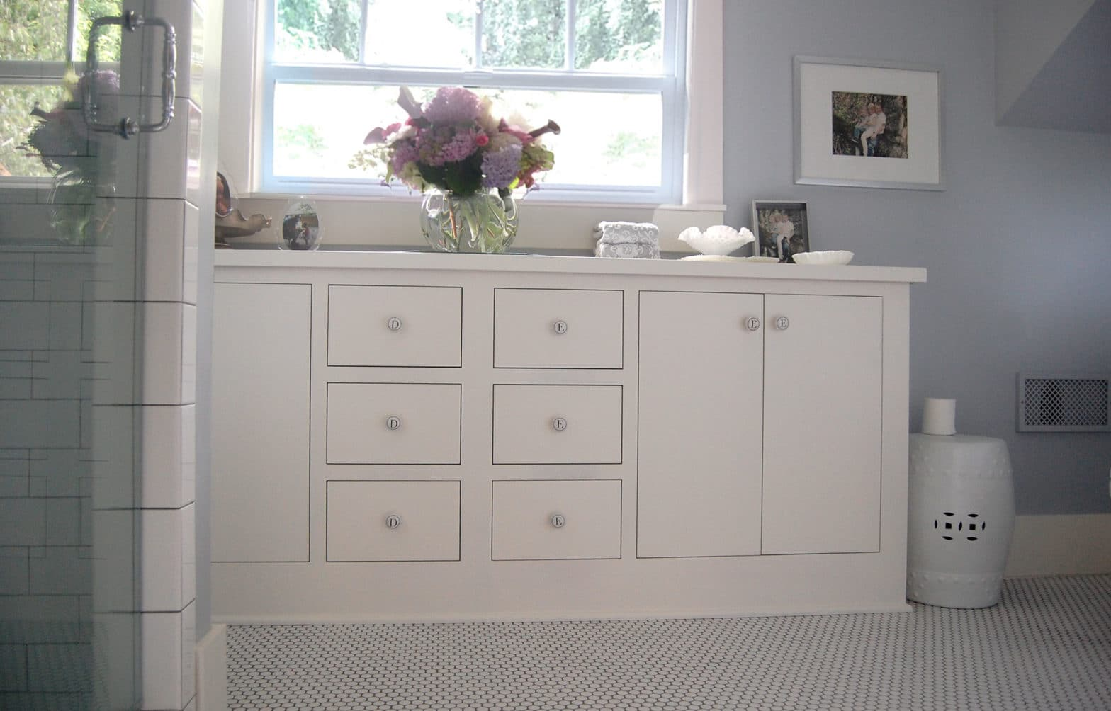 White Cabinets With Flowers In Bright Bathroom