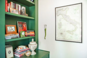 The corner of a green, built-in bookcase. The bookcase has various books, framed photos, and accessories.. There is also a map of Italy on the wall.