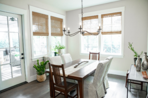 A dining room with a dark, transitional dining table, and bamboo shades on the windows. A door leads out to the deck.