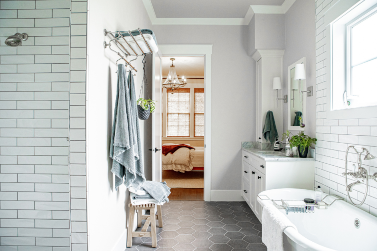 A master bedroom with a subway tiled shower, free standing tub and marble topped vanity.