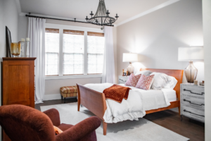 A master bedroom with a sleigh bed, white and rust colored bedding.
