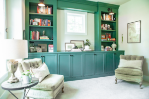 A home study with a green, built-in bookcase and two antique chairs.
